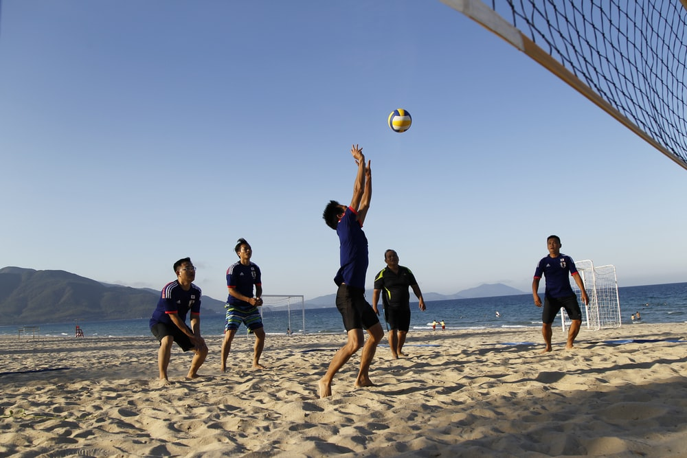 people playing volleyball under blue sky during daytime
