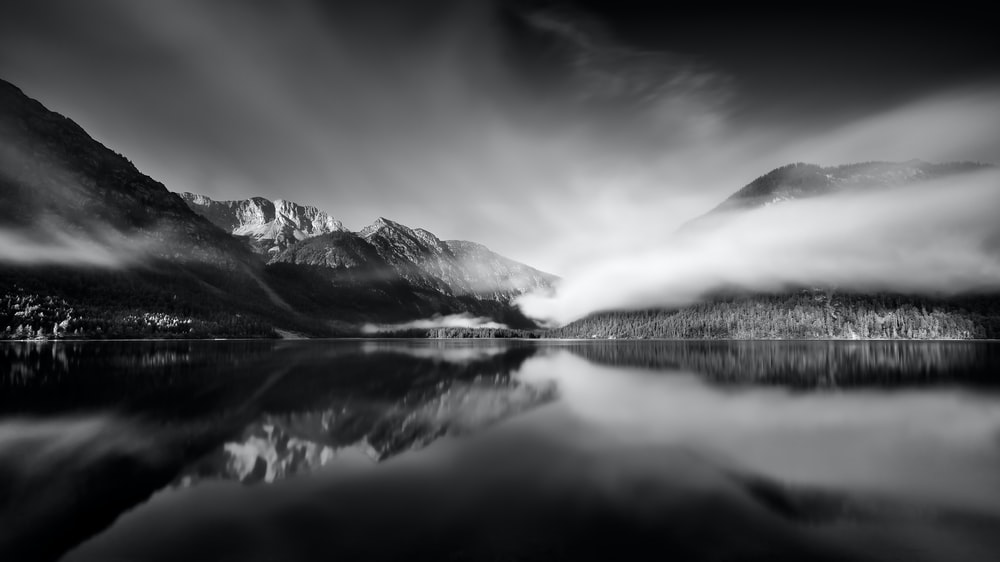 grayscale photo of snow covered mountain near body of water