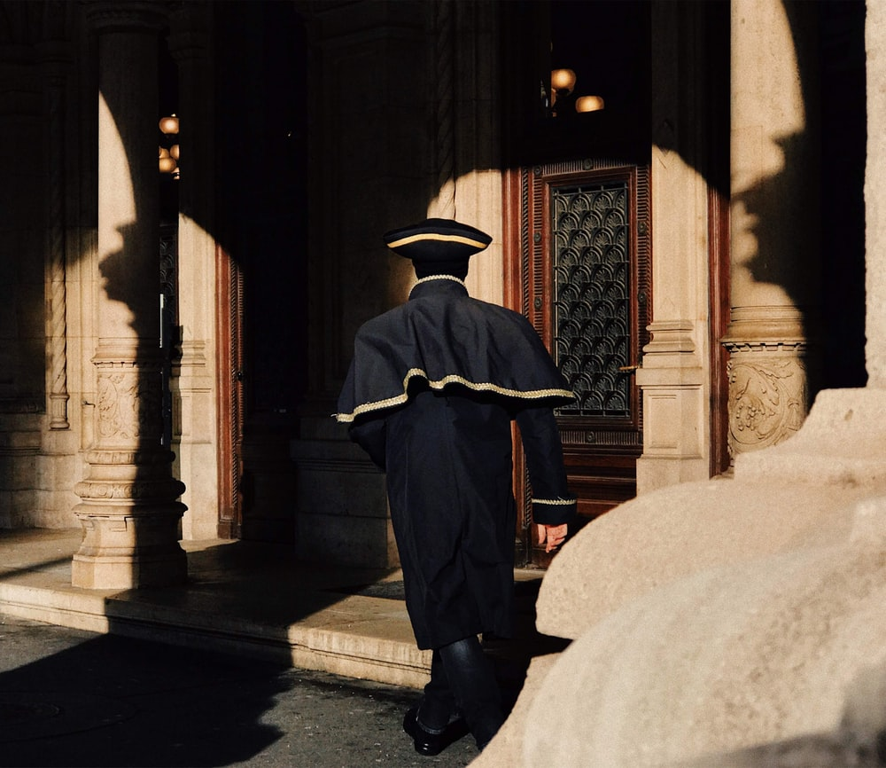 man in black coat and black hat sitting on concrete bench
