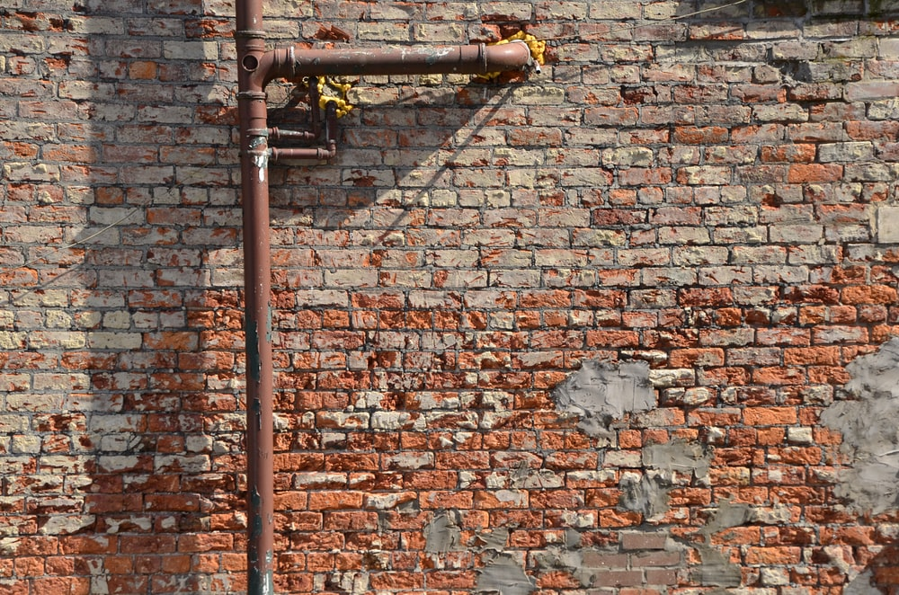 brown metal pipe on brown brick wall