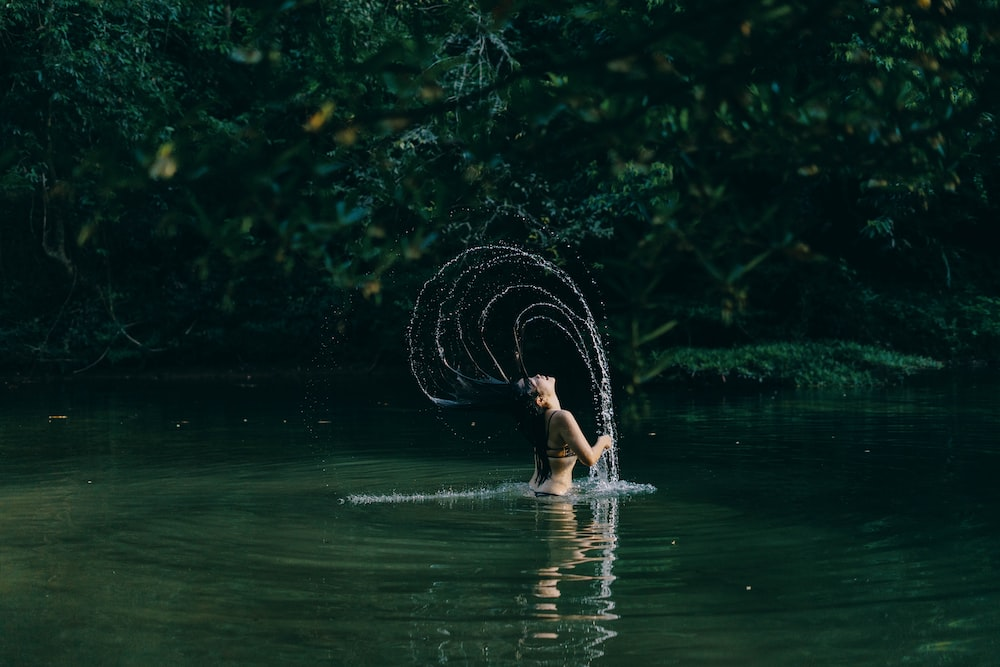 woman in water holding white string lights