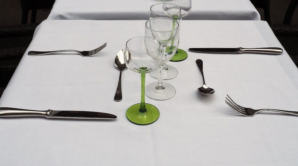 clear wine glass beside silver spoon and fork on white table