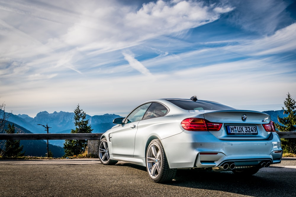silver mercedes benz coupe on brown dirt road under blue sky during daytime