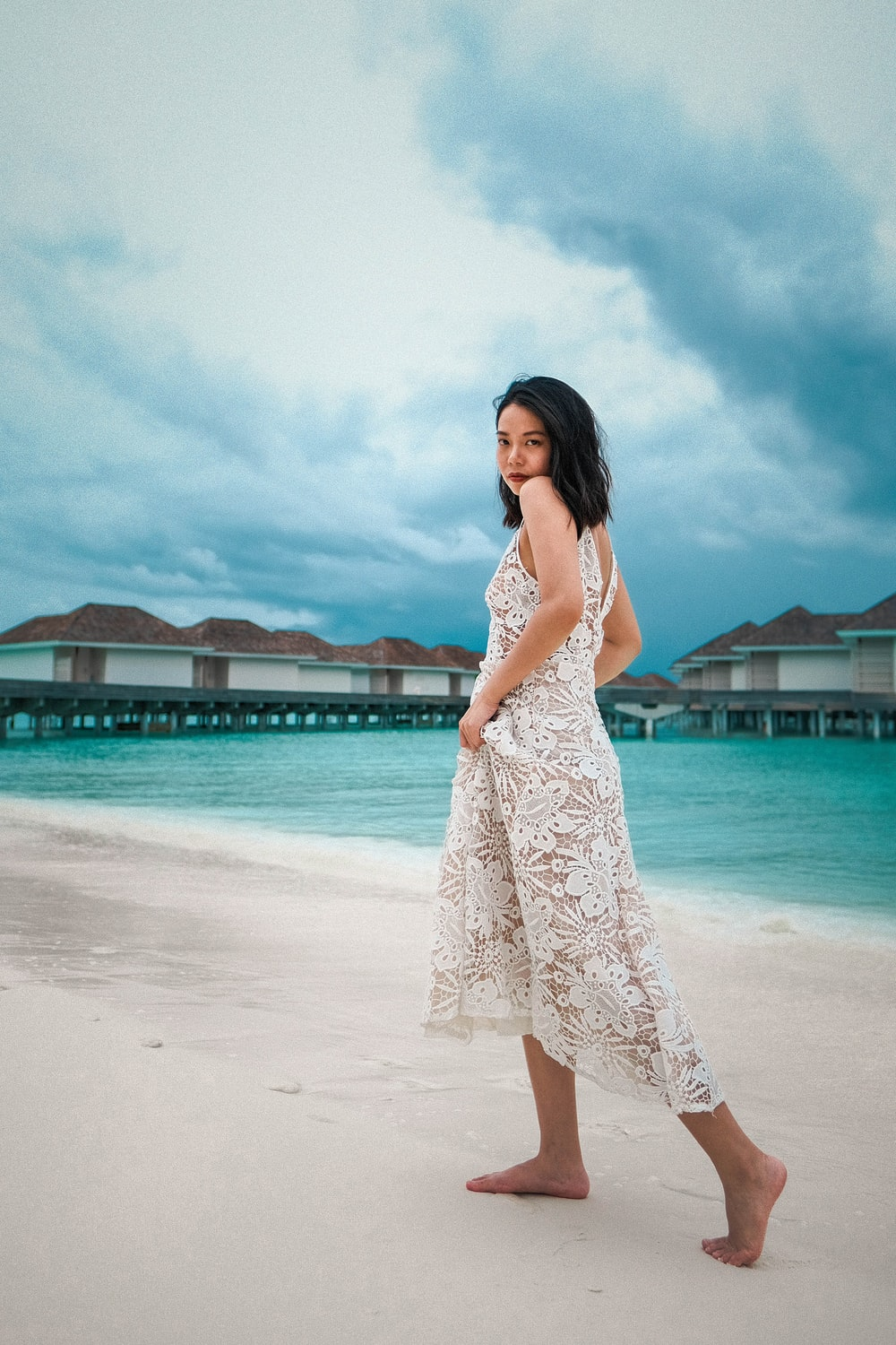 woman in white and blue floral sleeveless dress standing on beach during daytime