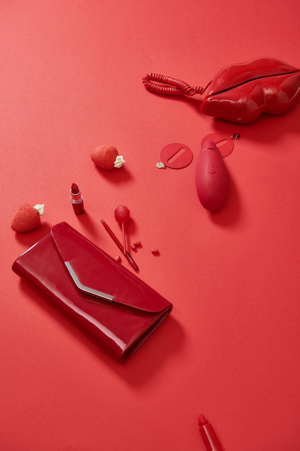 pink leather handbag beside red heart shaped ornament