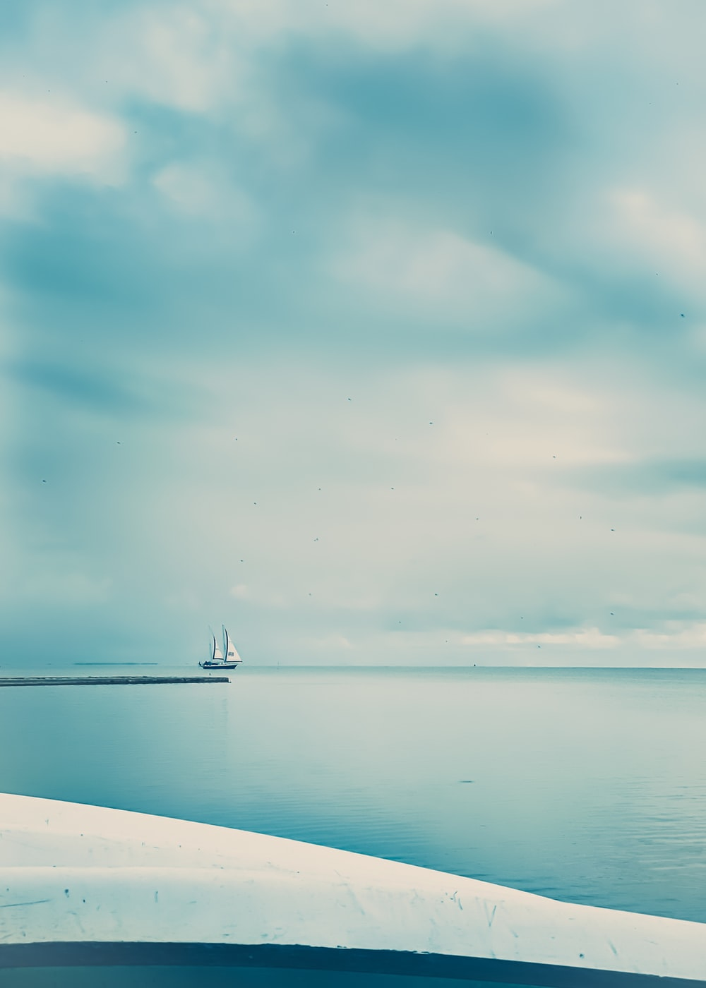 white boat on sea under blue sky during daytime