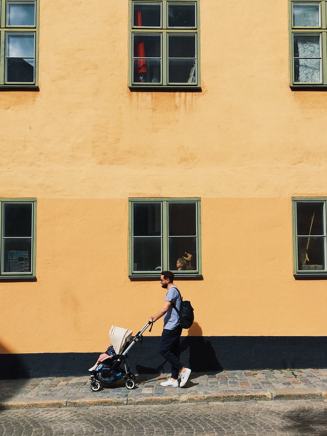 Daddy walking his baby in a stroller in front of one of Stockholm's emblematic creamy façades in Södermalm.