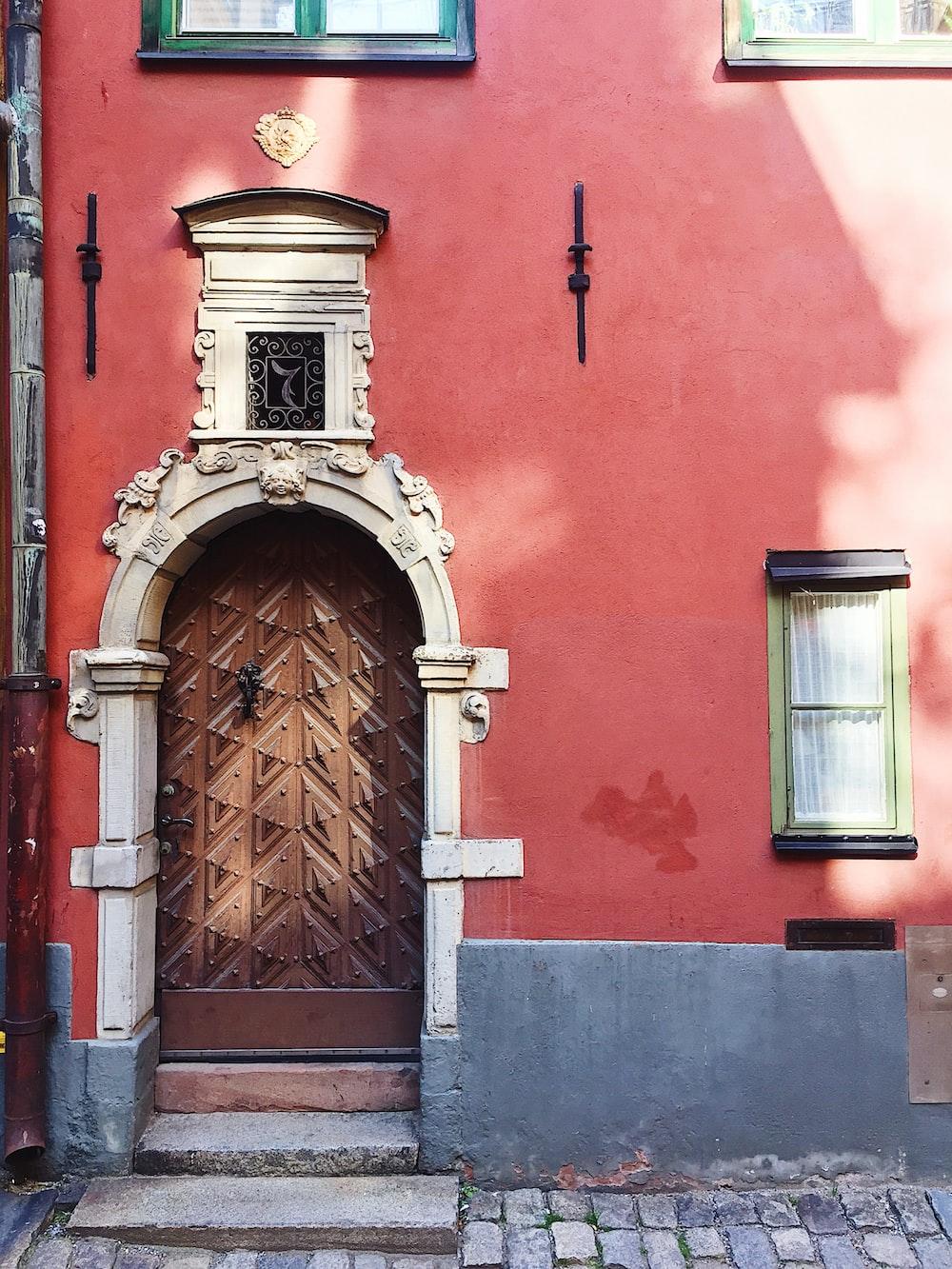 brown wooden door on red concrete building