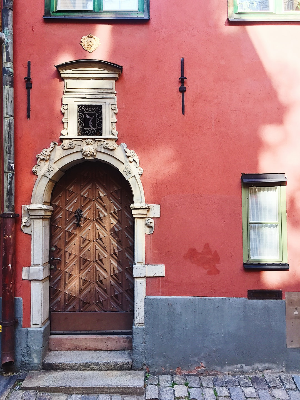 Beautiful door in a red façade from the streets of Gamla Stan in Stockholm, Sweden.
