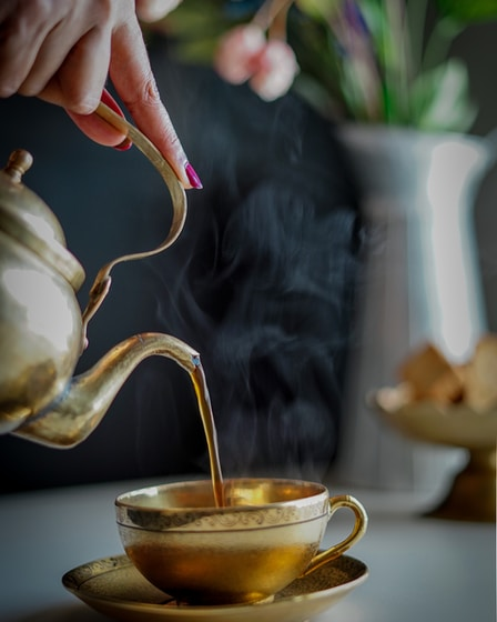 person pouring tea on white ceramic teapot