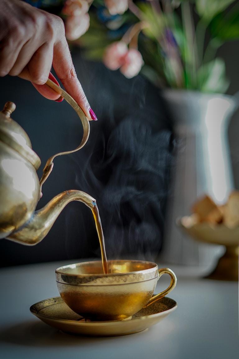 person pouring tea on white ceramic teapot