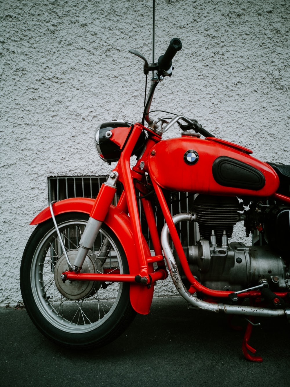 red and black motorcycle parked beside white wall