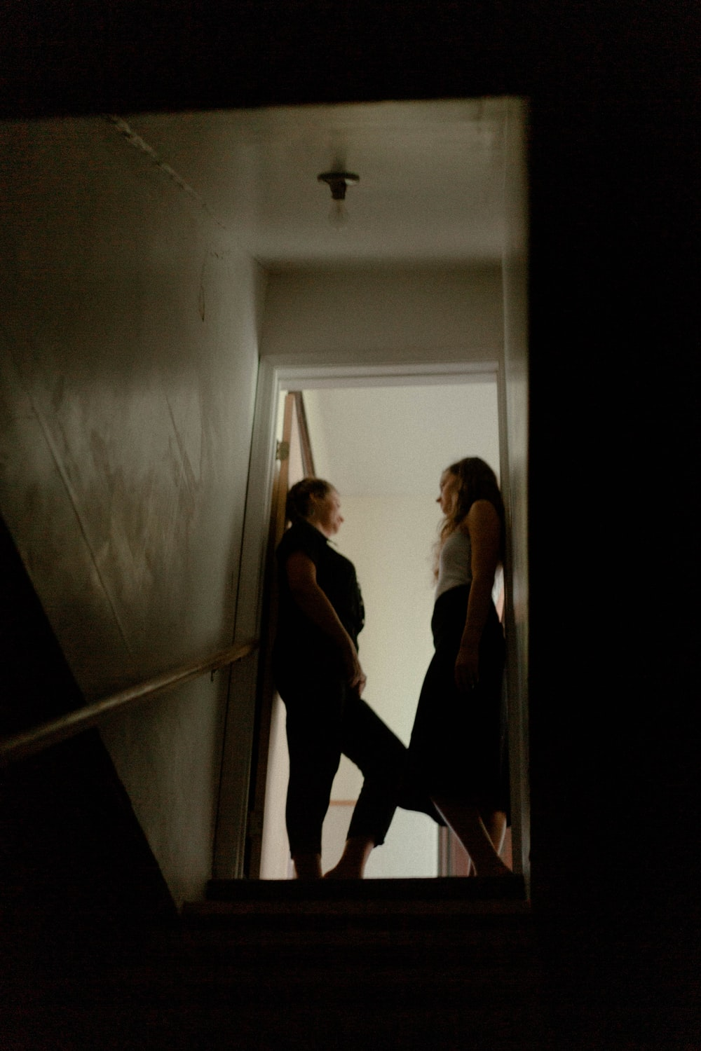 woman in black tank top and black pants standing on white hallway