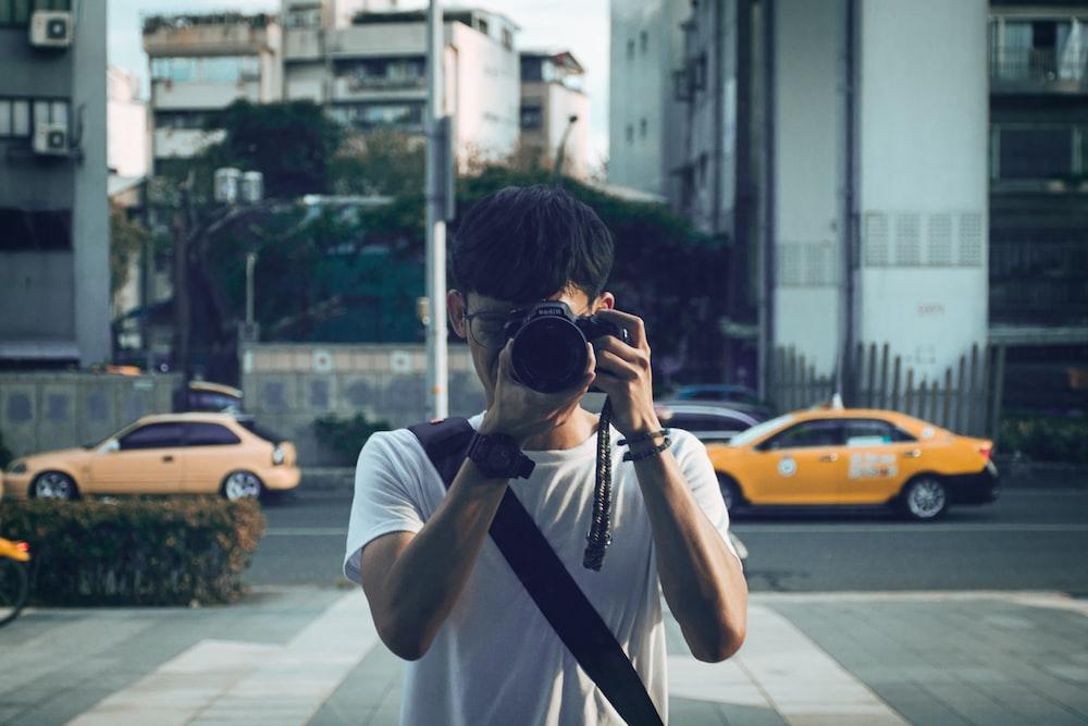 man in white t-shirt holding black camera