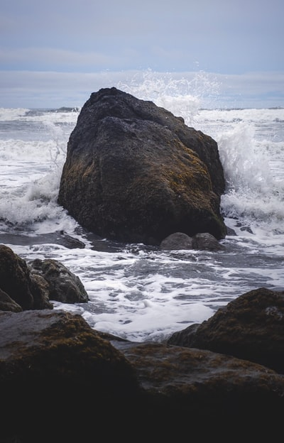 brown rock formation on sea water during daytime