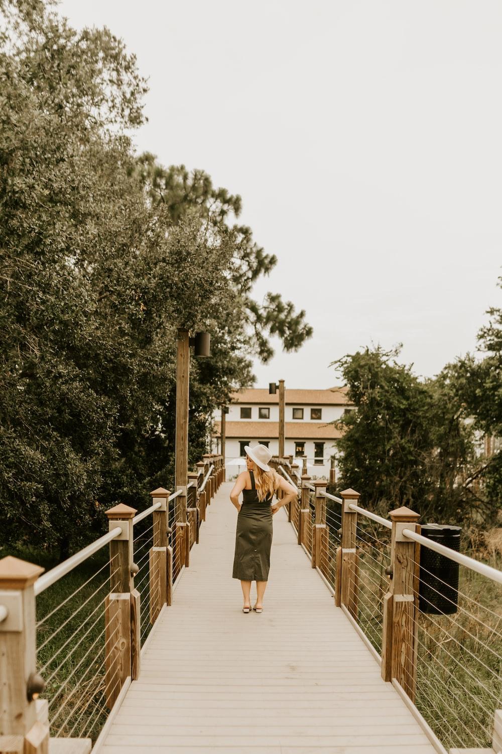 woman in brown coat walking on bridge during daytime