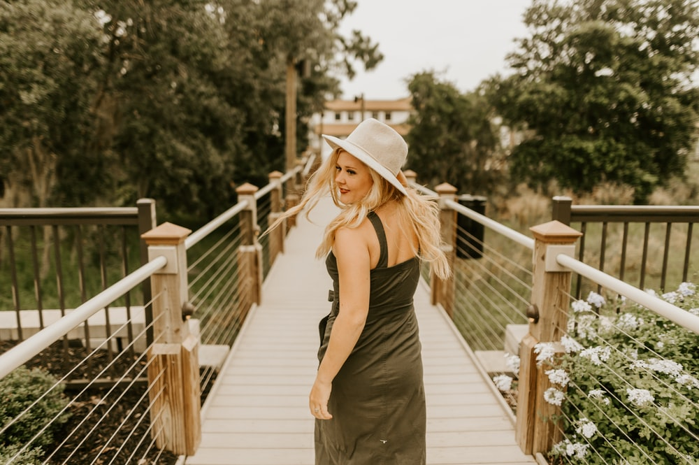woman in black spaghetti strap dress and brown hat standing on wooden bridge during daytime