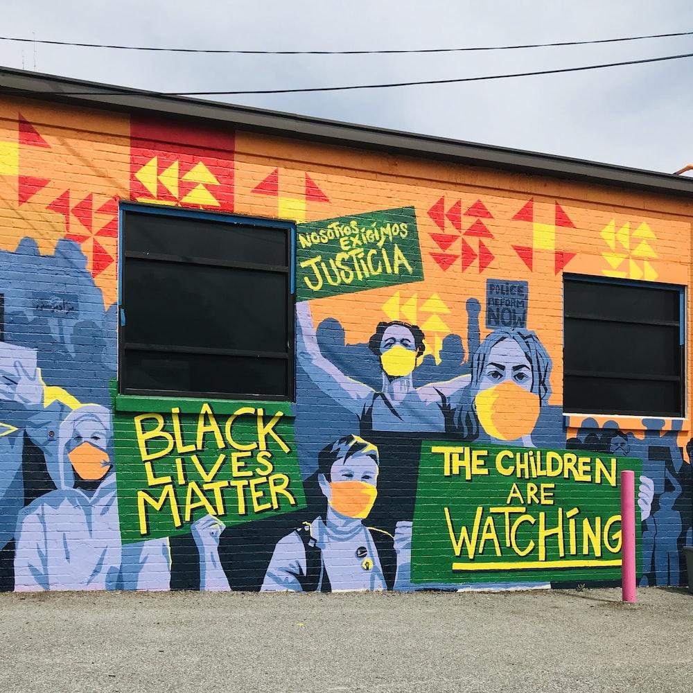 man in black jacket walking beside wall with graffiti