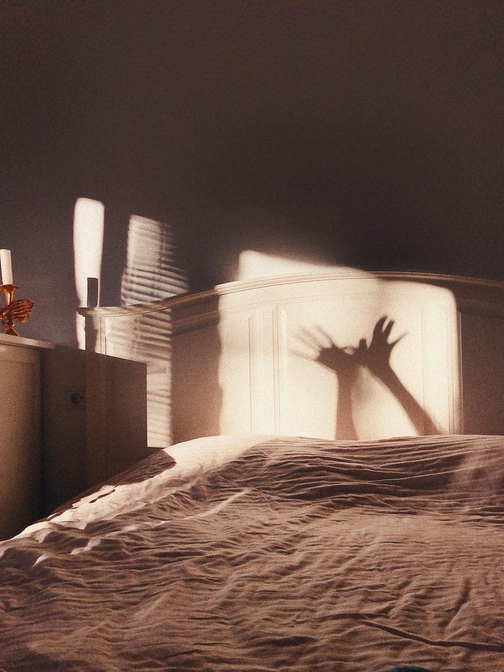 white bed linen near brown wooden drawer