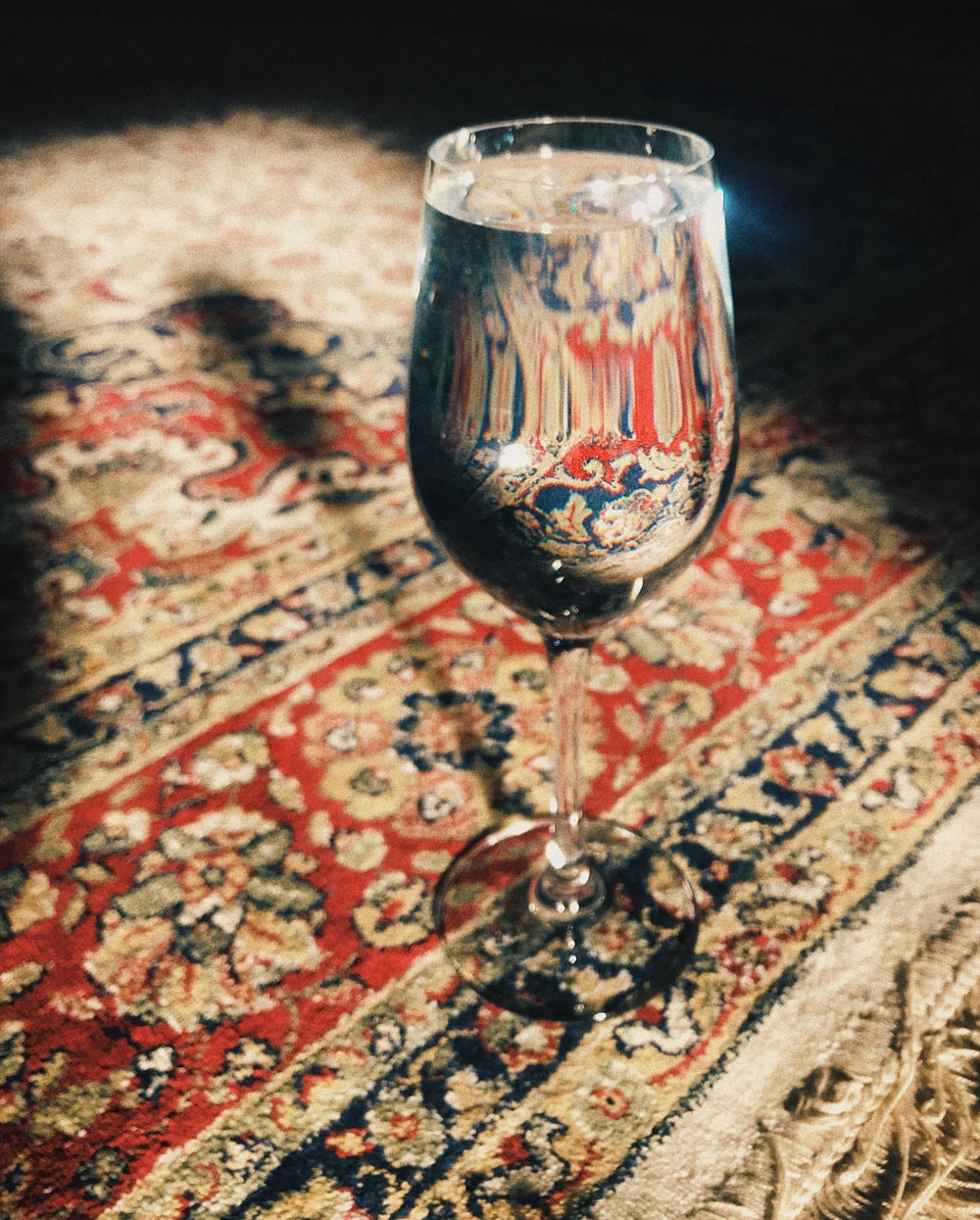 clear wine glass on red and brown floral textile