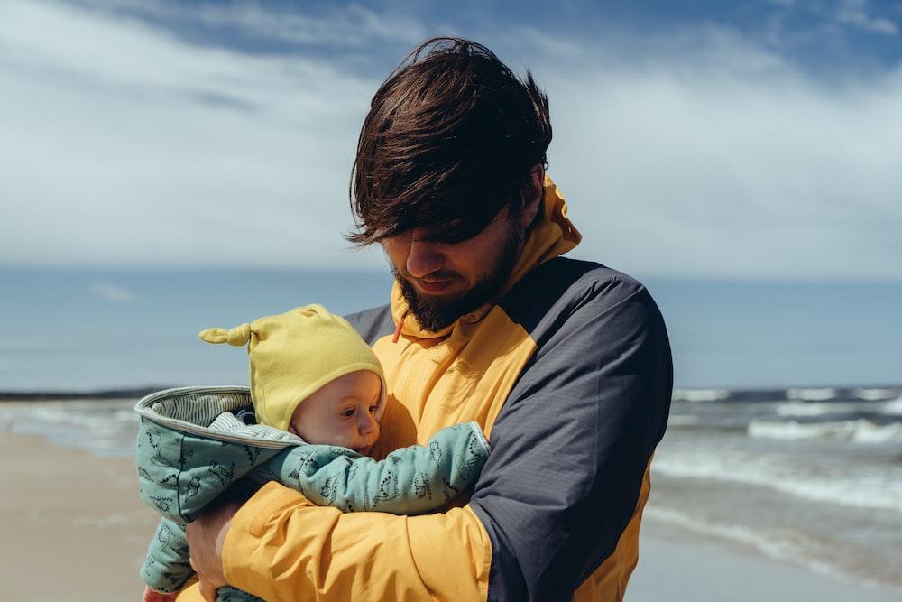 man in black jacket carrying baby in yellow hoodie
