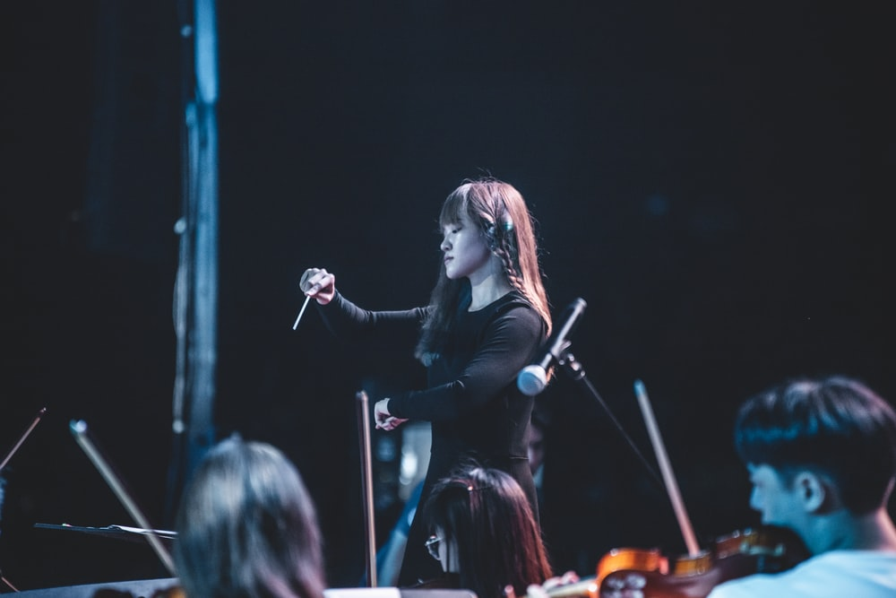 woman in black long sleeve shirt singing on stage