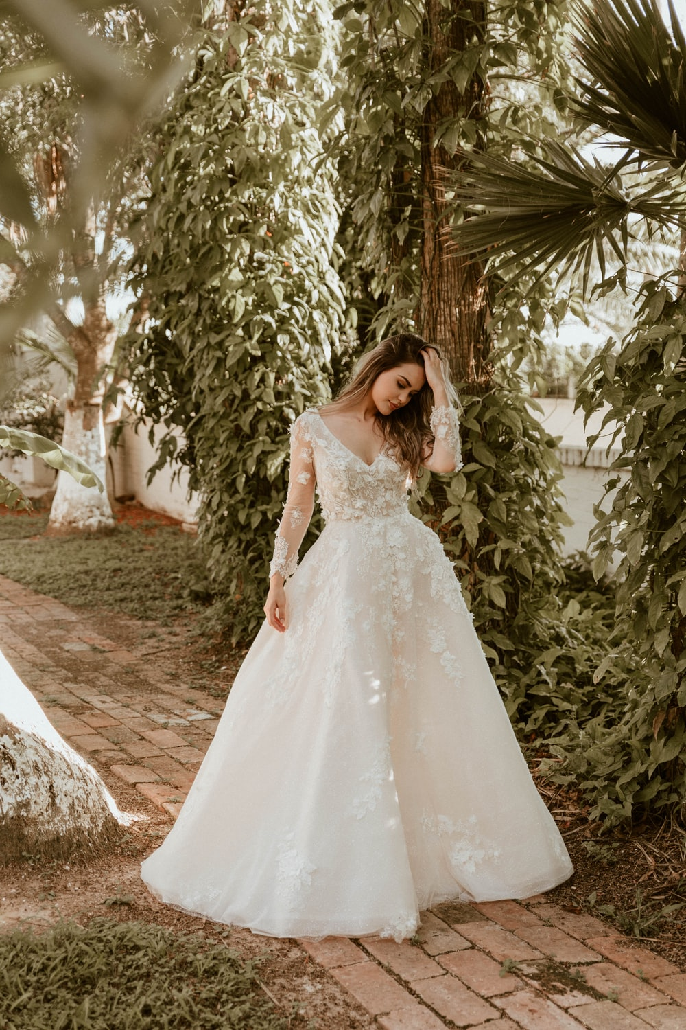 woman in white wedding dress standing near green trees during daytime