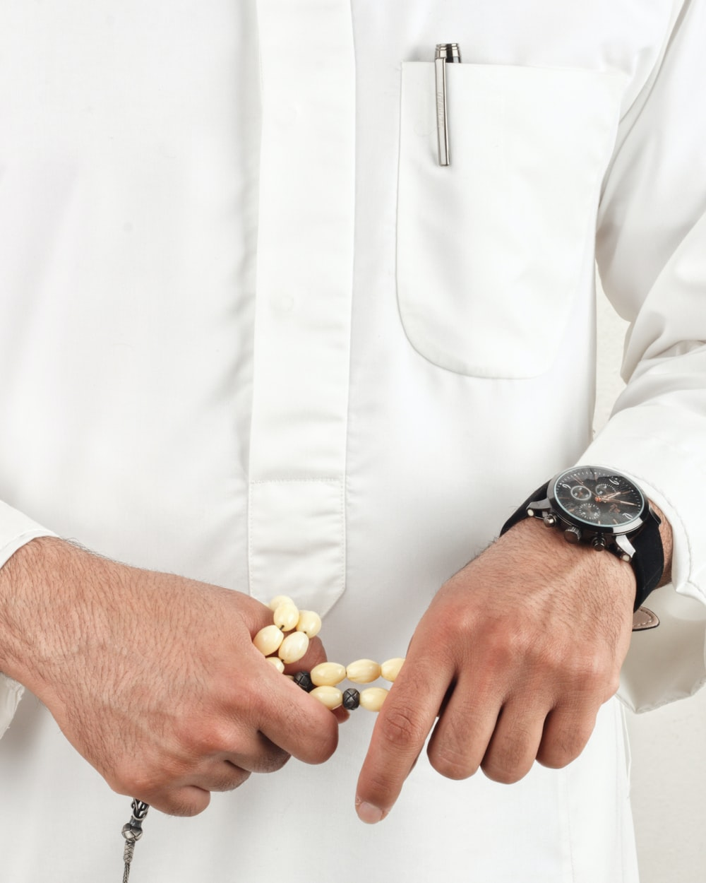 man in white dress shirt wearing black round analog watch