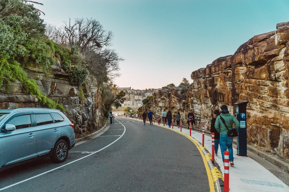 people walking on road near brown rock formation during daytime