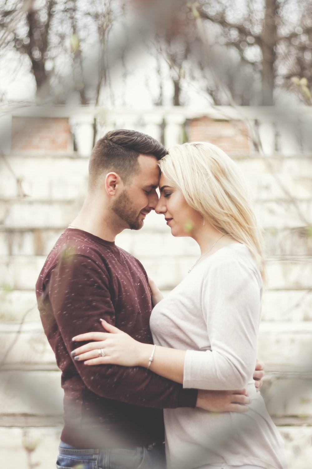 man in maroon crew neck shirt kissing woman in white long sleeve shirt
