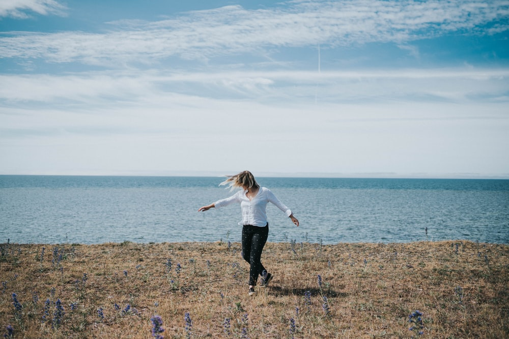 girl in white shirt and black pants walking on green grass field near body of water