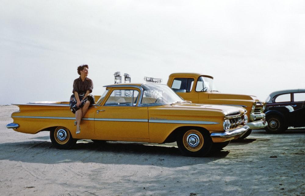 man in black jacket standing beside yellow vintage car