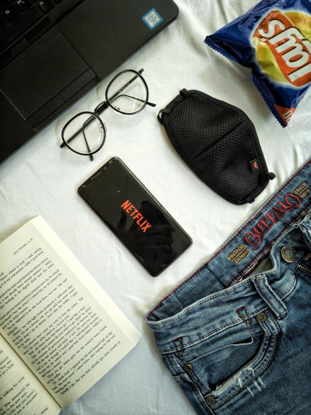 black framed eyeglasses beside black leather pouch and blue denim jeans