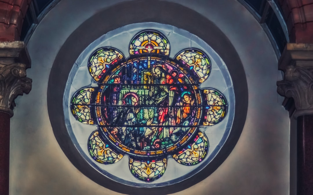 Stained-glass rose window set in marble at St. Patrick's Church in the Cathedral Quarter of Belfast (Aug., 2019).