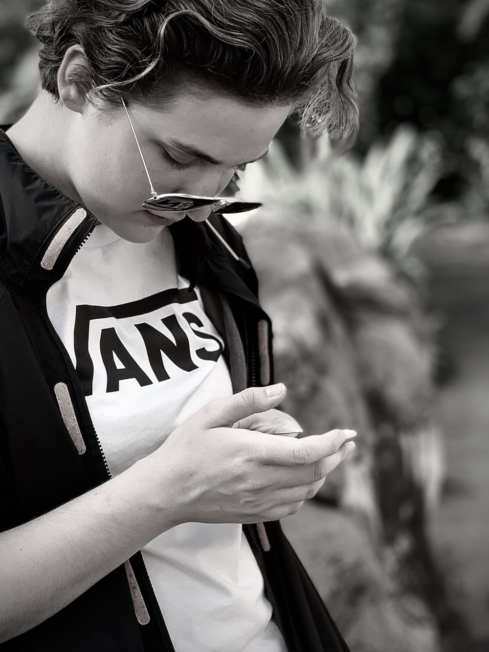 woman in black and white shirt holding smartphone