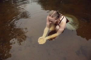 woman in black bikini kneeling on water