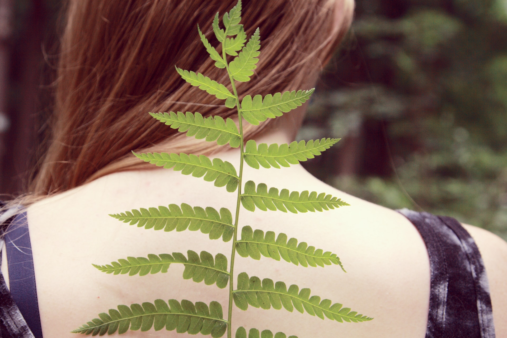 woman in black and white tank top with green leaf on her back