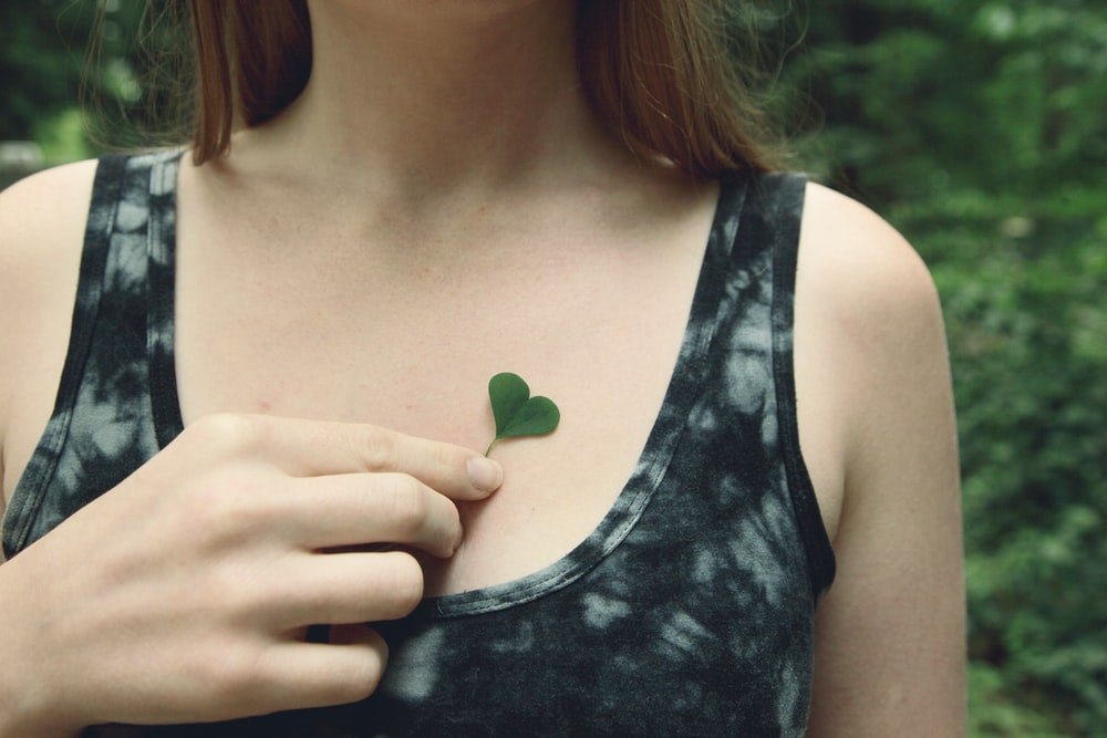 woman in black tank top holding green leaf