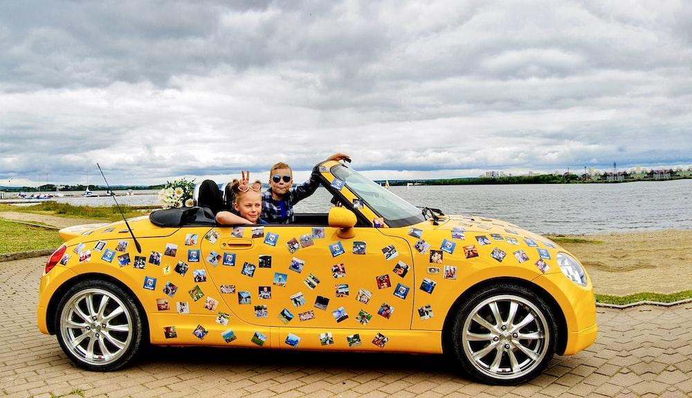 2 women riding yellow convertible car