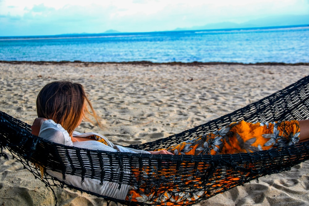 woman in white shirt lying on hammock on beach during daytime