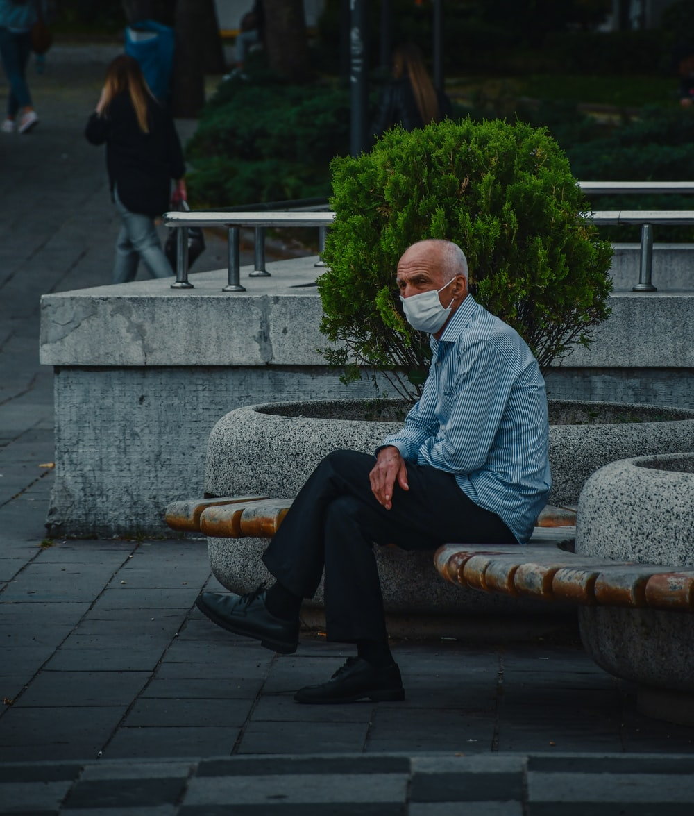 man in white dress shirt and black pants sitting on gray concrete bench