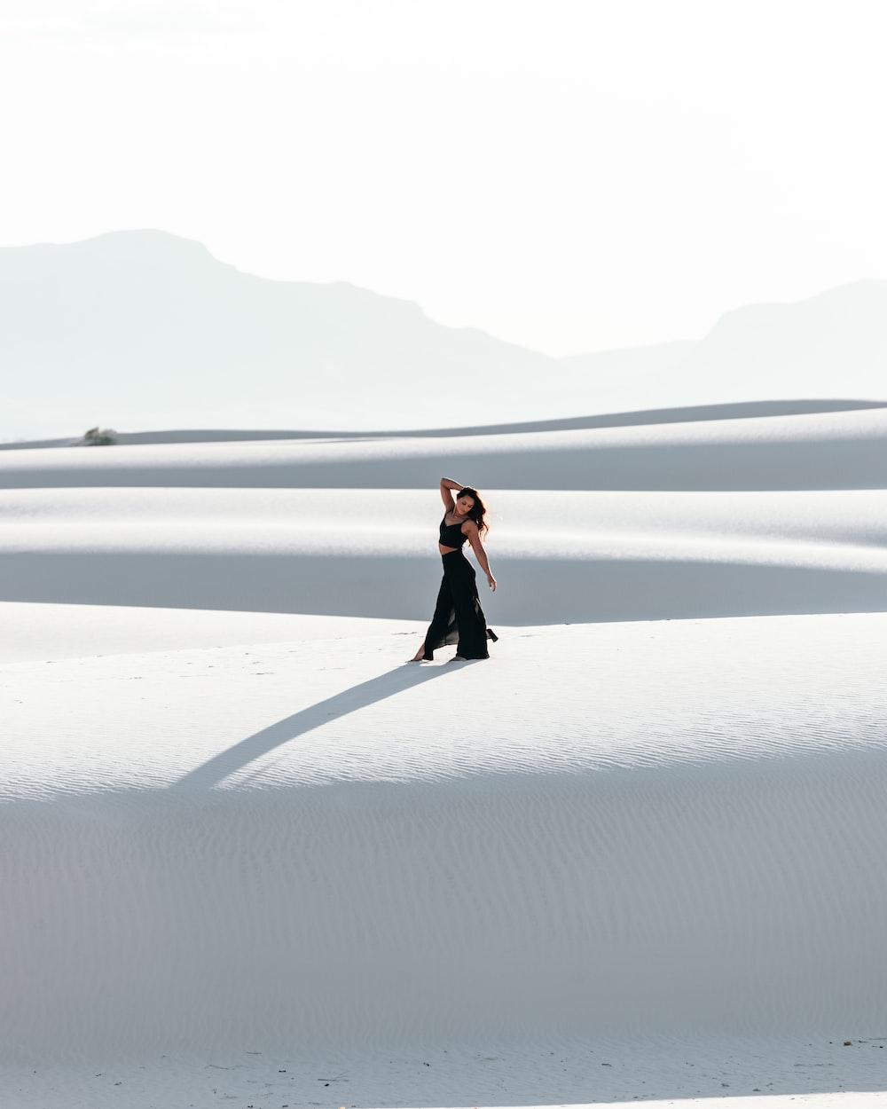woman in black dress walking on white sand during daytime