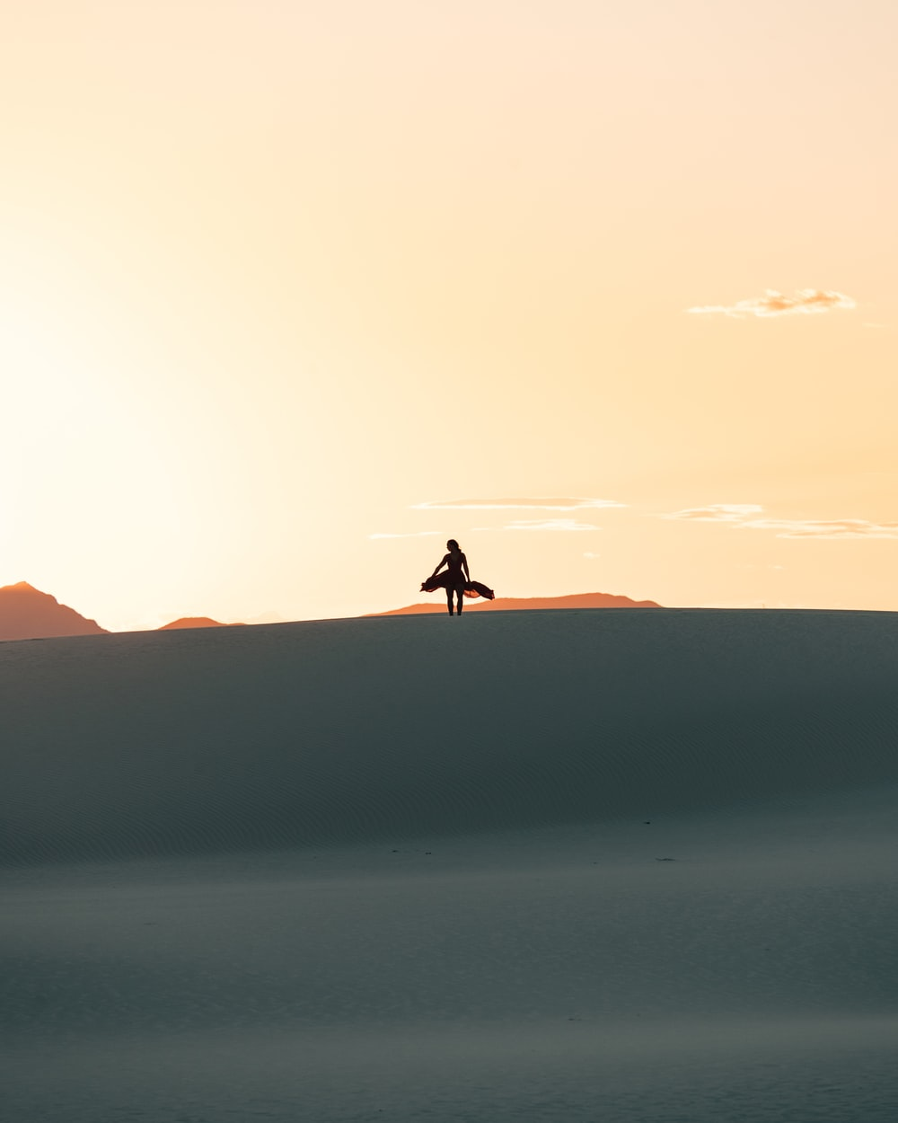 silhouette of person walking on desert during daytime