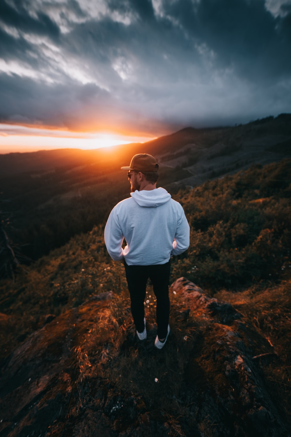 man in white sweater standing on brown grass field during sunset
