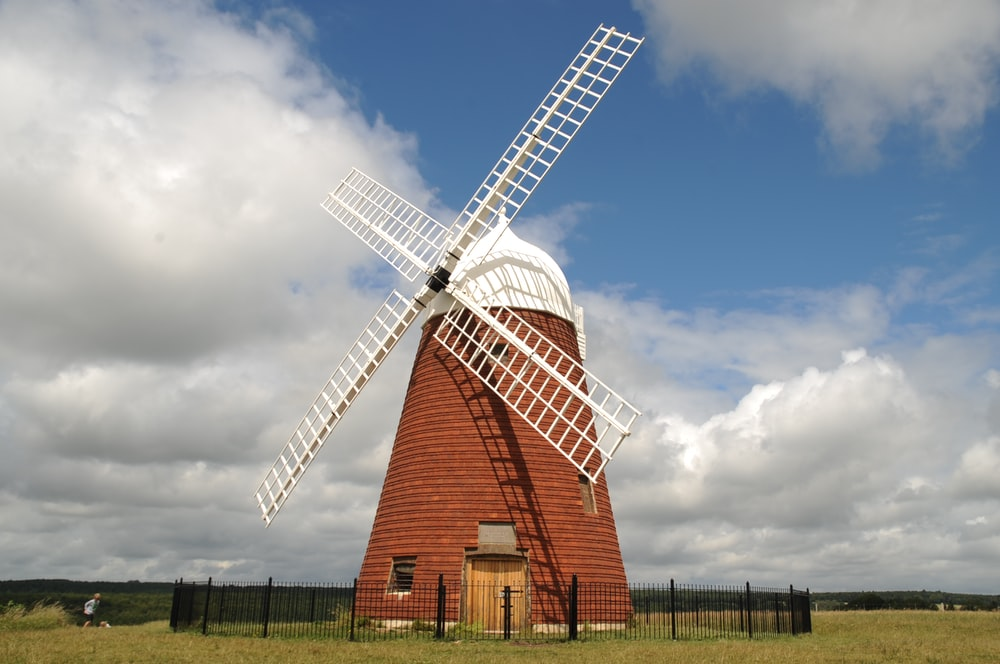 brown and white windmill under blue sky during daytime