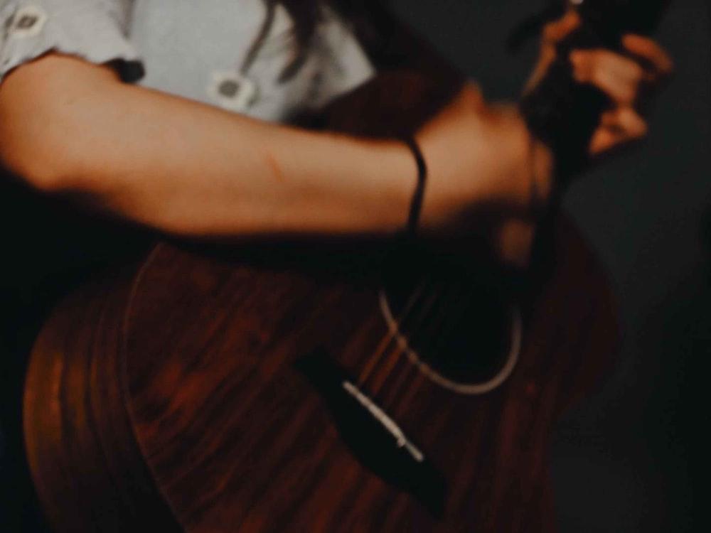 man in white t-shirt playing guitar