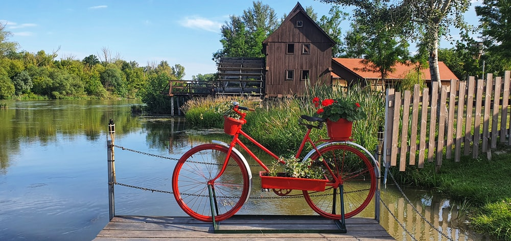 red city bike parked beside brown wooden house near body of water during daytime