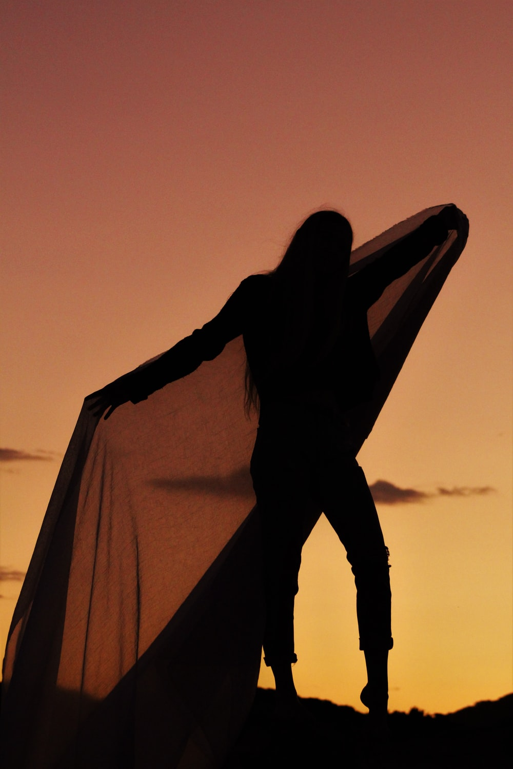silhouette of woman covering her face with brown textile