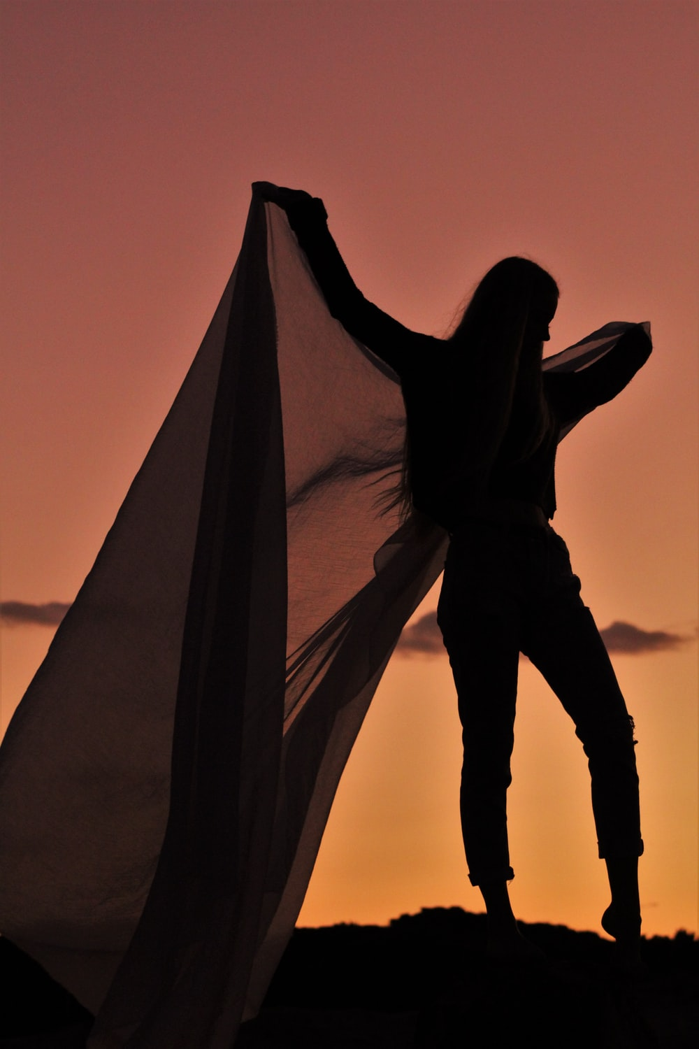 silhouette of woman holding textile