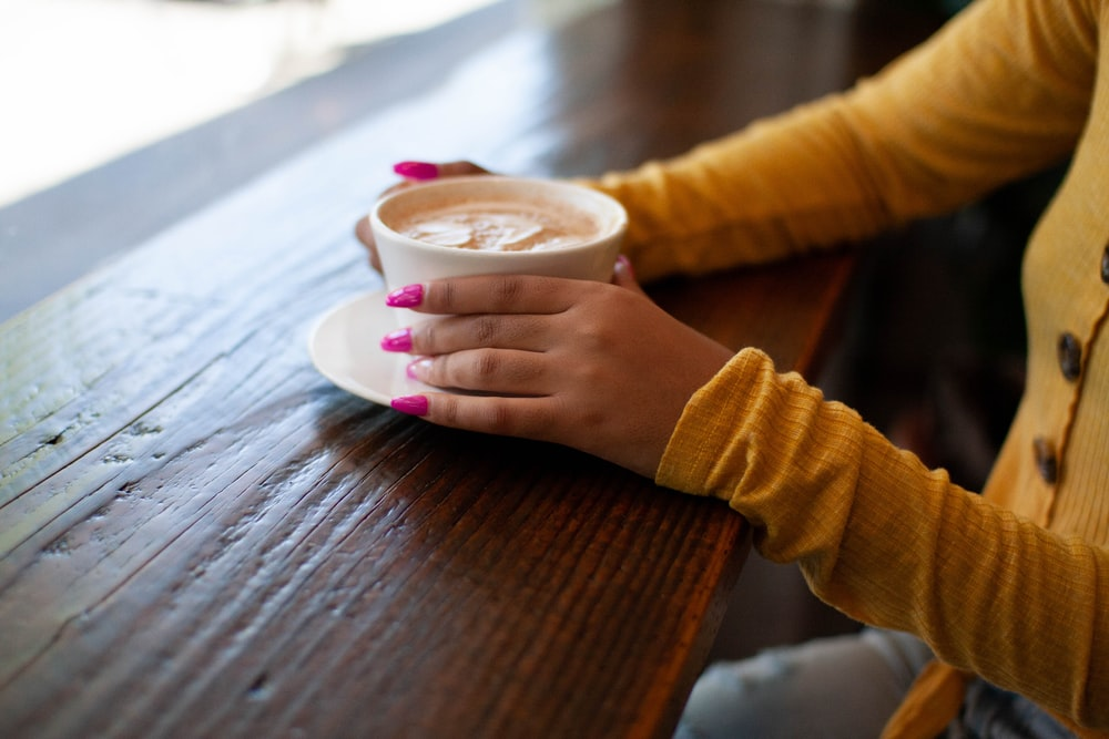 person in brown sweater holding white ceramic mug with brown liquid